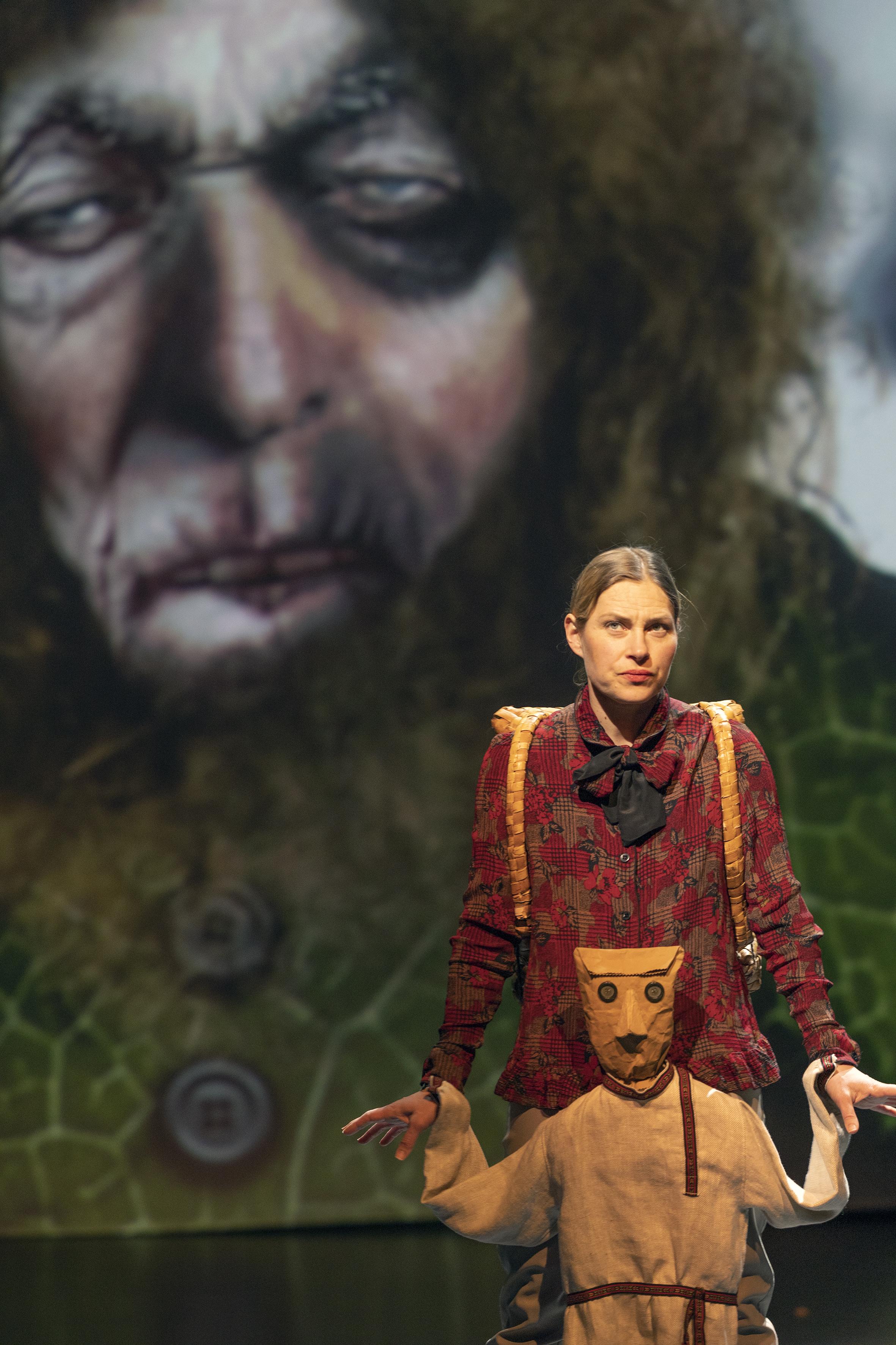Valokuvan taka-alalla on piirroskuva karvaisesta jättiläisestä ja etualalla on näyttelijä ja Antti Puuhaara -nukke.
