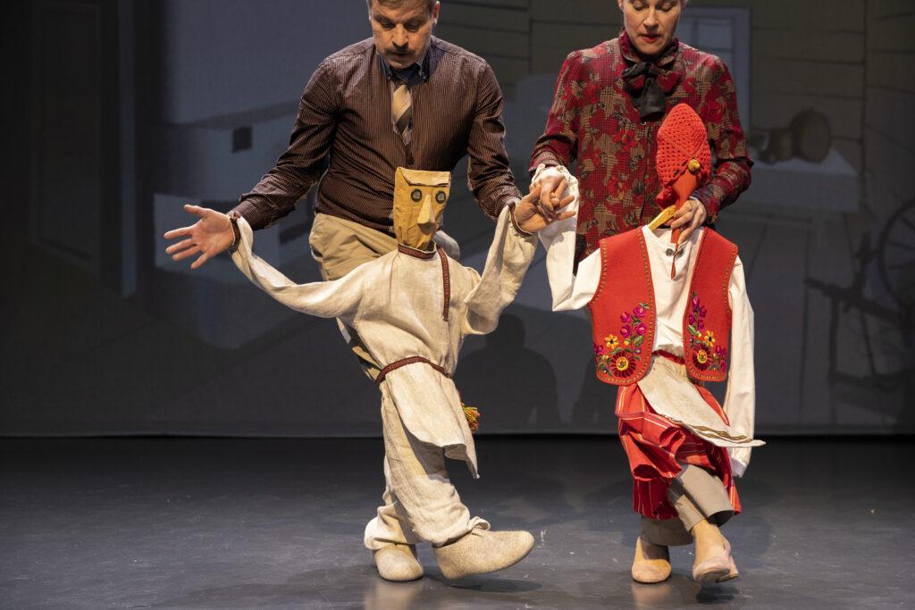 Valokuvassa kaksi näyttelijää tanssii Antti Puuhaaraa ja Riikka-Hannaa esittävien nukkejen kanssa.