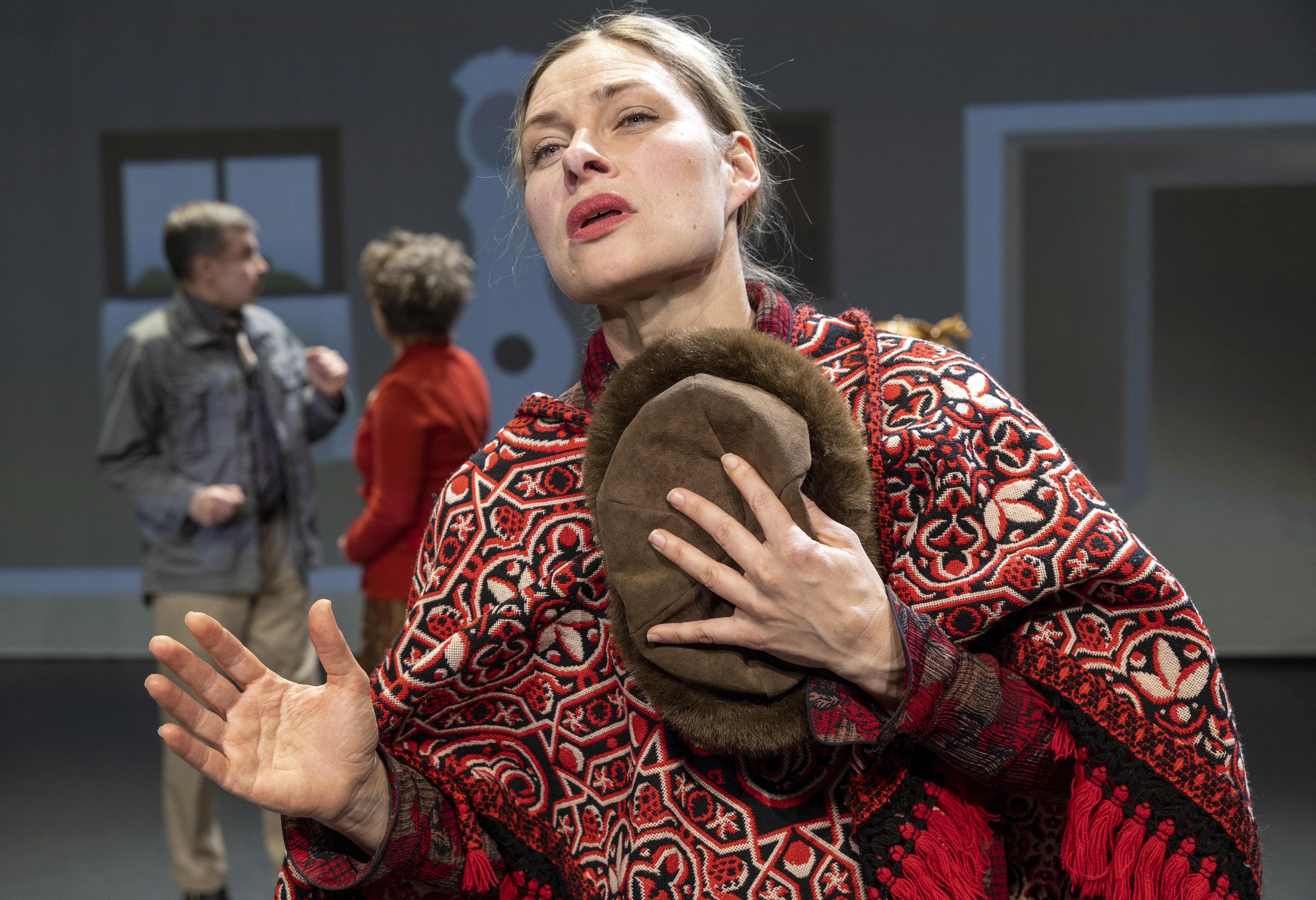 Valokuvassa on nainen jolla on punaisenkirjava poncho ja kädessään karvalakki. Nainen siristää silmiään ja katsoo kaukaisuuteen.