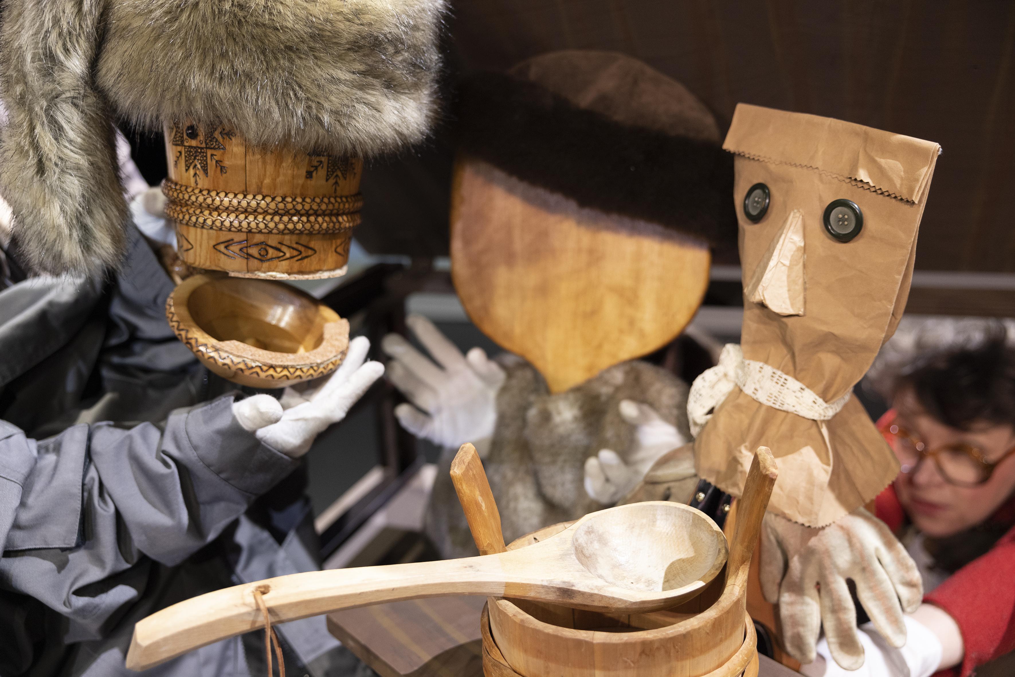 Valokuvassa on turkiskauppias ja Antti Puuhaara. Turkiskauppiaan hahmo on luotu karvalakista ja puisesta kolpakosta. Antti puuhaara hahmo on luotu paperipussista.