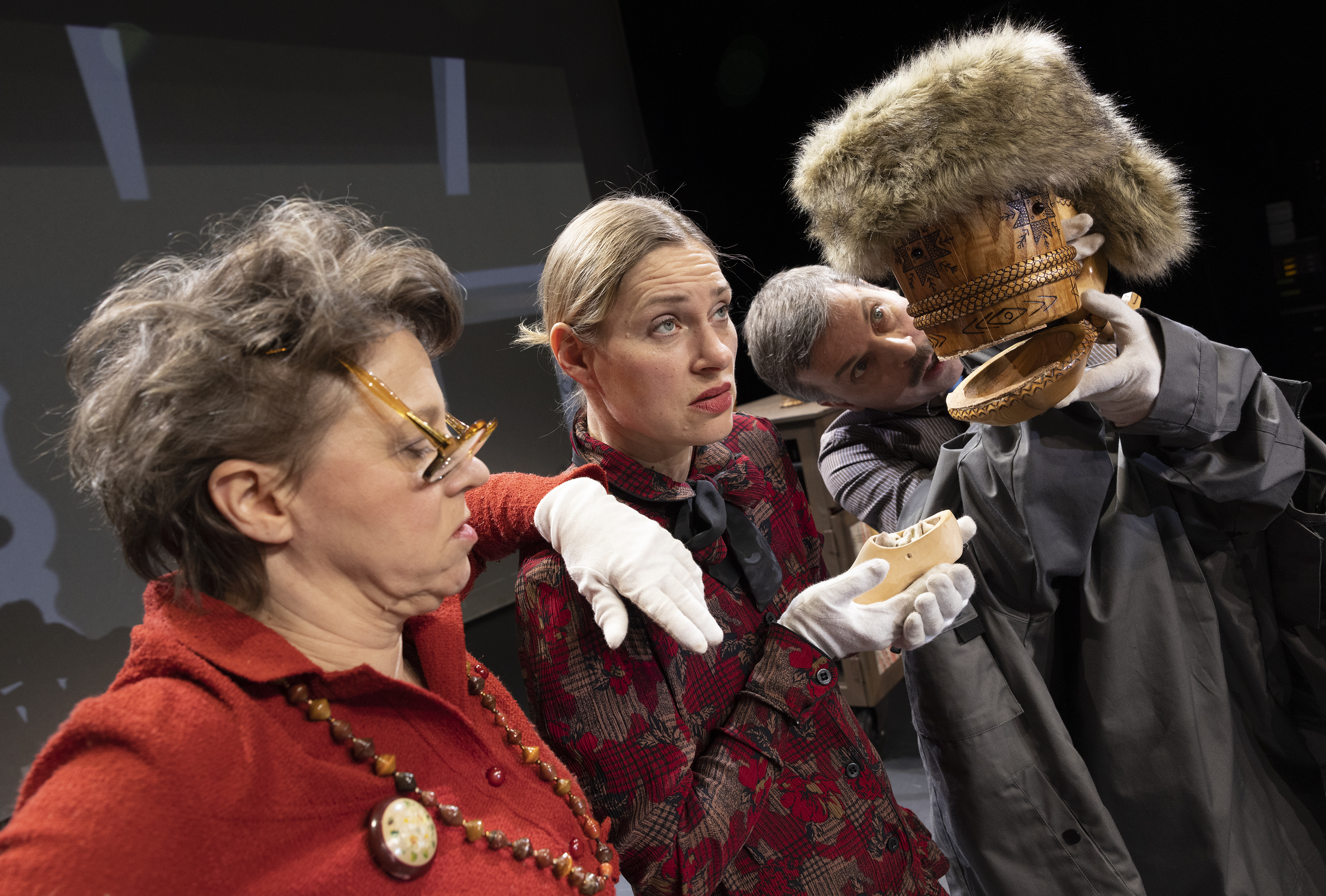 Valokuvassa kaksi näyttelijää esittää Antti Puuhaaran vanhempia. He näyttävät väsyneiltä. Puisen kolpakon ja karvalakin avulla luotu nukke esittää Turkiskauppiasta, joka puhuu Antti Puuhaaran vanhemmille.
